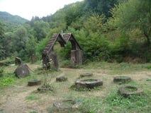 Vaciamiento con algunas ruinas de la piedra redonda en un bosque en Armenia Fotografía de archivo
