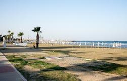 Vacie de la playa de Finikoudes de la estación con los paraguas doblados en Larnaca Foto de archivo