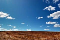 Vacie el campo cosechado bajo el cielo azul nublado Imagenes de archivo
