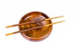 Vacie el cuenco de madera con los palillos en el fondo blanco Foto de archivo libre de regalías