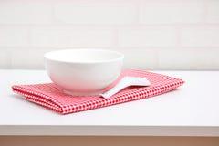 Vacie el cuenco y la cuchara blancos en mantel rojo Fotos de archivo