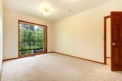 Vacie el sitio blanco con la puerta de madera y la alfombra beige. Imagen de archivo libre de regalías