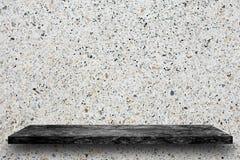 Vacie el top de estantes de piedra de mármol negros en fondo del terrazo, fotos de archivo