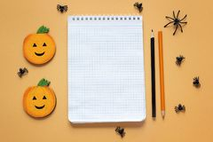 Vacie la libreta abierta con las decoraciones de Halloween en backdro anaranjado Imagen de archivo