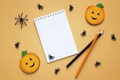 Vacie la libreta abierta con las decoraciones de Halloween en backdro anaranjado Fotografía de archivo