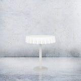 Vacie la mesa redonda con el mantel en fondo concreto Fotografía de archivo