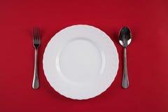 Vacie la placa de cena blanca con la cuchara de sopa de plata de la bifurcación y del postre aislada en fondo rojo del mantel con Fotos de archivo