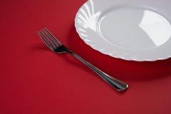 Vacie la placa de cena blanca con la cuchara de sopa de plata de la bifurcación y del postre aislada en fondo rojo del mantel con Imagenes de archivo
