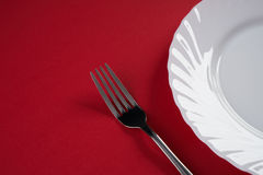Vacie la placa de cena blanca con la cuchara de sopa de plata de la bifurcación y del postre aislada en fondo rojo del mantel con Fotografía de archivo libre de regalías