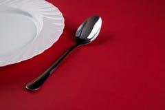 Vacie la placa de cena blanca con la cuchara de sopa de plata de la bifurcación y del postre aislada en fondo rojo del mantel con Fotos de archivo libres de regalías