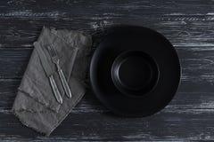 Vacie la placa negra, la bifurcación y el cuchillo en la servilleta, fondo oscuro rústico Visión desde arriba, proyección horizon Imagen de archivo libre de regalías