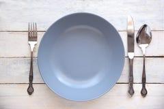 Vacie la placa y los cubiertos azules en una tabla de madera blanca de un restaurante rústico Imagen de archivo