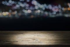 Vacie la plataforma y el bokeh de madera de la tabla en la noche Imagenes de archivo