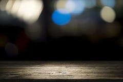 Vacie la plataforma y el bokeh de madera de la tabla en la noche Foto de archivo libre de regalías