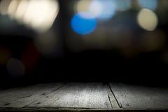 Vacie la plataforma y el bokeh de madera de la tabla en la noche Fotografía de archivo libre de regalías