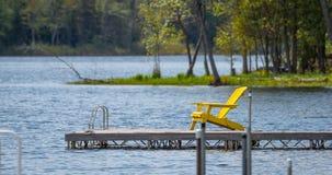 Vacie la silla de cubierta amarilla en un muelle en el lago Fotos de archivo libres de regalías