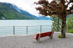 Vacie la silla roja y ajardine de la ciudad de Brienz en Suiza Imagen de archivo libre de regalías