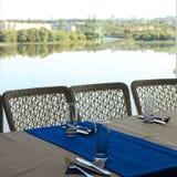 Vacie la tabla de banquete mitad-servida en restaurante con las servilletas, vidrios, bifurcaciones, cuchillos, opinión baja del  Fotografía de archivo libre de regalías