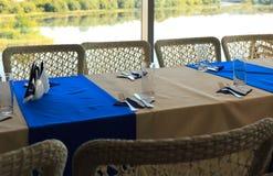 Vacie la tabla de banquete mitad-servida en restaurante con las servilletas, vidrios, bifurcaciones, cuchillos, opinión baja del  Fotografía de archivo