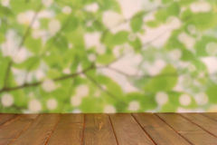 Vacie la tabla de madera de la cubierta con el fondo del bokeh del follaje Foto de archivo