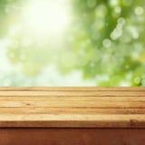 Tabla de madera vacía de la cubierta con el bokeh del follaje Foto de archivo libre de regalías