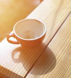 Vacie la taza de café roja en la tabla de madera con luz del sol Imágenes de archivo libres de regalías