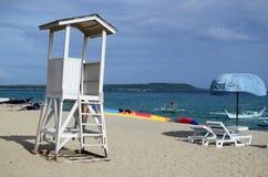 vacie la torre blanca del salvavidas con el cielo nublado en la playa blanca de la arena Imágenes de archivo libres de regalías