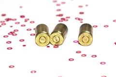 Vacie las cáscaras de la bala de 9m m sobre el fondo blanco con los pequeños objetos del hexágono rojo Imagenes de archivo