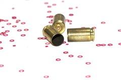 Vacie las cáscaras de la bala de 9m m sobre el fondo blanco con los pequeños objetos del hexágono rojo Imagen de archivo libre de regalías