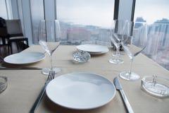 Vacie las placas blancas en la tabla en un restaurante con una opinión grande de la ventana Imagen de archivo libre de regalías
