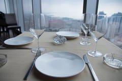 Vacie las placas blancas en la tabla en un restaurante con una opinión grande de la ventana Imagen de archivo
