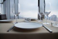 Vacie las placas blancas en la tabla en un restaurante con una opinión grande de la ventana Fotografía de archivo libre de regalías