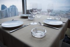 Vacie las placas blancas en la tabla en un restaurante con una opinión grande de la ventana Imágenes de archivo libres de regalías
