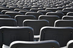 Vacie las sillas plásticas negras alligned en muchas filas Fotos de archivo
