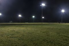 Vacie los campos de fútbol atléticos en la noche con las luces encendido Imágenes de archivo libres de regalías