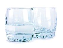 Vacie y mitad de los vidrios de agua aislados en blanco Fotos de archivo libres de regalías