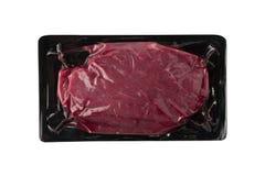 Vacuüm zwart plastic pak met vers geïsoleerd rundvleeslapje vlees stock foto