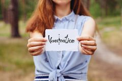 Vacunación - mujer joven que sostiene la tarjeta de papel con palabra, atención sanitaria y la medicina imagen de archivo libre de regalías
