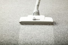 Vacuum cleaner. On the grey carpet with the dust