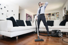 Vacuum cleaner. Man sweating cleans the floor of the house Royalty Free Stock Images