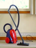Vacuum Cleaner. A hose-type vacuum cleaner sitting on the floor beneath a window royalty free stock photography