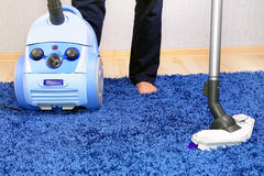 Vacuum cleaner in action-men cleaner a carpet. Stock Image