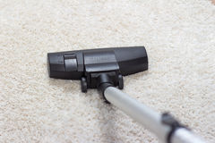 Vacuum cleaner being used to vacuum a carpet Stock Image