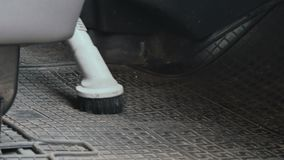 Vacuum cleaner clean the cabin of car. Close-up. Car washman cleans the interior of automobile. Worker uses vacuum cleaner to clean the cabin of car from dirty stock video footage