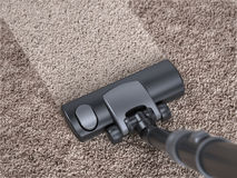 Vacuum cleaner cleans dirty carpet - house cleaning concept Royalty Free Stock Images