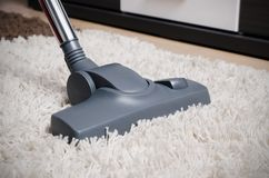 Vacuum cleaner cleans the white shaggy carpet. Royalty Free Stock Photography
