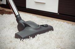 Vacuum cleaner cleans the white shaggy carpet. Stock Photography