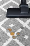 Vacuum cleaner and coins on gray carpet Stock Image