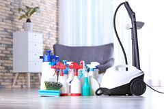 Vacuum cleaner and detergents on floor. Indoors stock photo