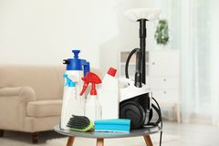 Vacuum cleaner and detergents. On table indoors royalty free stock photography